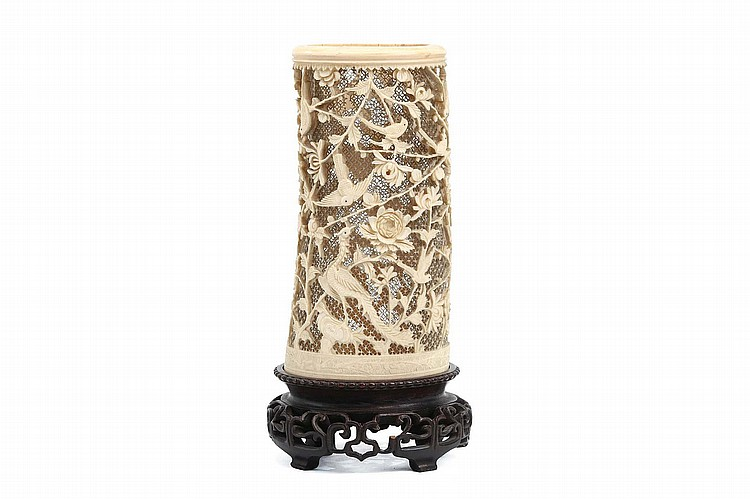 A CHINESE CARVED IVORY 'HUNDRED BIRDS' BRUSHPOT.   Qing Dynasty.   Carved and pierced with birds among scrolling foliage, carved and pierced wood stand, 27cm H.   Provenance: Collection of Bernard Buckman (1910 – 1991).   ? ???????