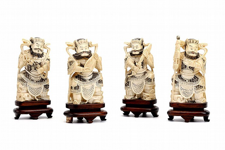 FOUR CHINESE IVORY CARVINGS DEPICTING DHRITARASTRA, VIDRADHAKA, VIRAPAKSA AND VAISRAVANA. Late Qing Dynasty. Each of the Buddhist four Heavenly Kings seated on a rocky base, wooden stand, 10.5cm H. (4) Provenance: Collection of Bernard Buckman (1910 – 1991). ?? ??????