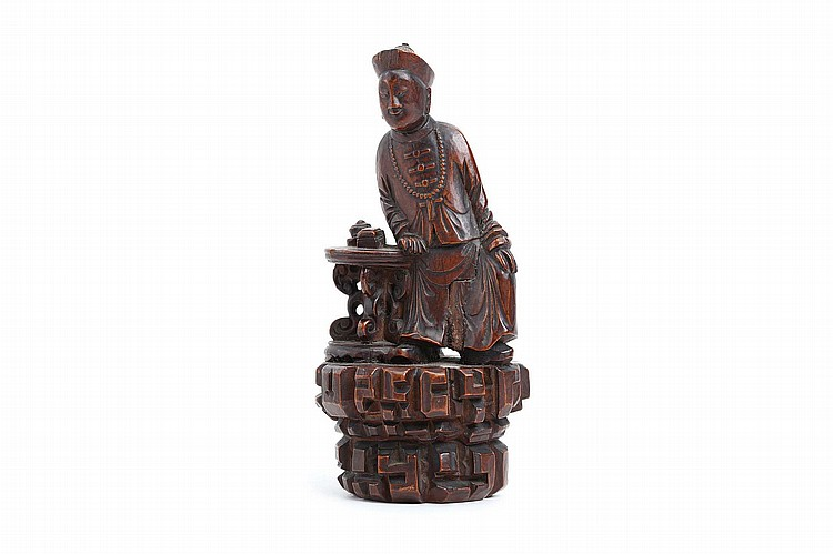 A CHINESE CARVED WOOD EXPORT FIGURE OF A MANCHU FIGURE.   Qing Dynasty.   Seated at a table, on a rockwork base, 22cm H.   ? ????????