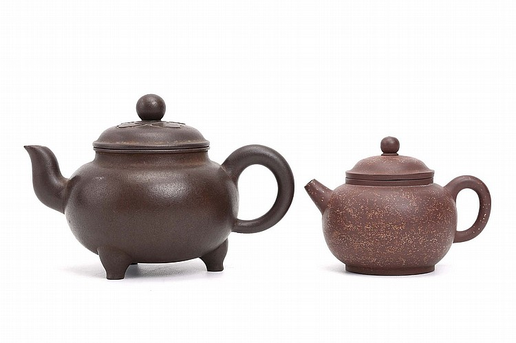TWO CHINESE YIXING ZISHA TEAPOTS AND COVERS.   One on short tripod feet with Zhou Guizhen (1943 –) seal to base, the other with Hou Youwan seal, 11.5cm / 9cm H. (2)   ?????????    ??????????????????    ????????????????
