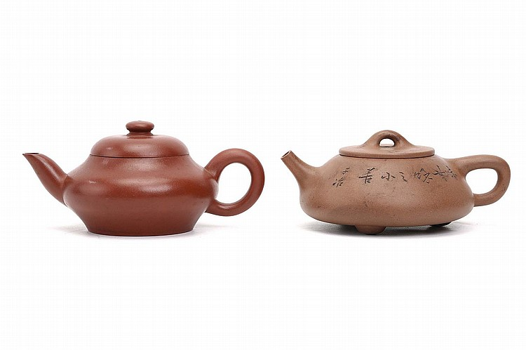 TWO CHINESE YIXING ZISHA TEAPOTS AND COVERS. One with a hand carved inscription to base, signed Meng Chen, the other raised on tripod feet, inscribed around the conical body, and signed with an alias of Wu Dacheng  signed 8cm H. (2) ????????? ????????????? ??? ???????????? ??????????