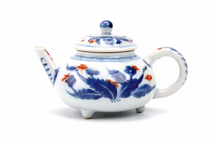 A CHINESE TRIPOD IMARI TEAPOT AND COVER. Qing Dynasty, Kangxi era. Raised on three short feet, with a squat body and upward pointing spout, decorated in blue and white with flowering branches, embellished in iron red enamel with further flower heads,