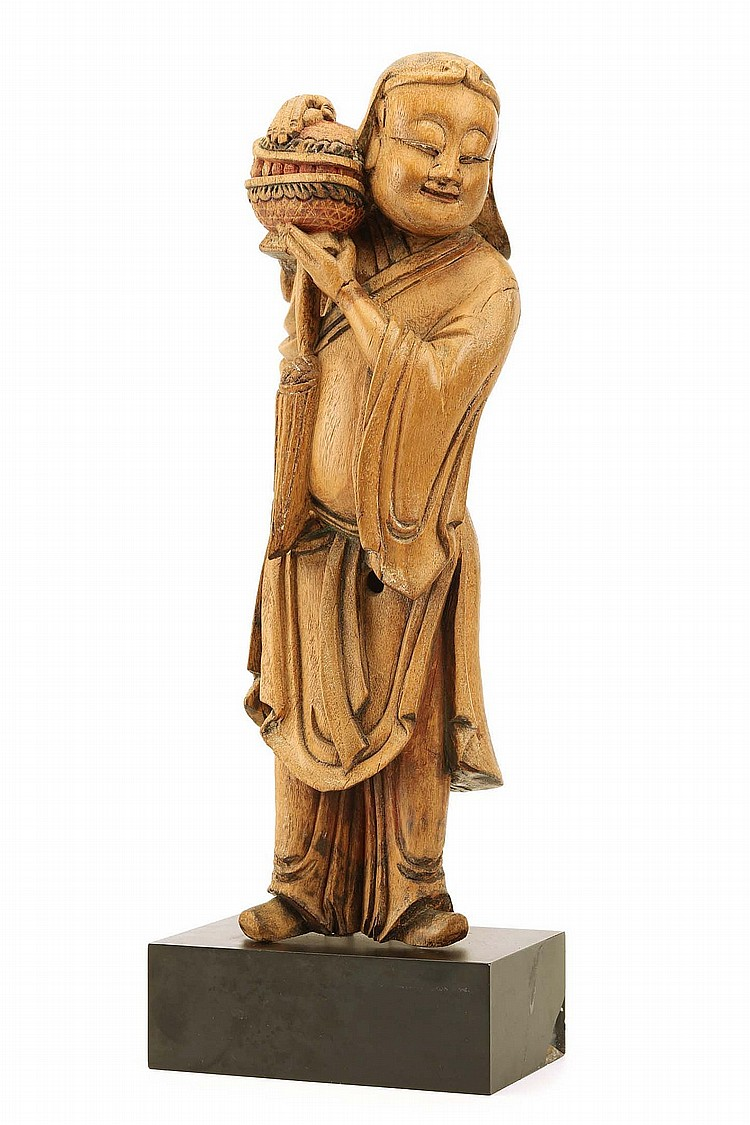 A CHINESE CEDARWOOD CARVING OF A BOY. Qing Dynasty, 18th / 19th Century. Standing in loose fitting robes, raising a box to his right shoulder, 37cm H. ?18-19?? ???????