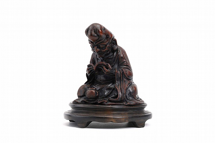 A CHINESE BAMBOO CARVING OF A LUOHAN. 18th / 19th Century. Seated cross legged in long flowing robes, consulting a book, wood stand, 11cm H. ?18-19?? ??????