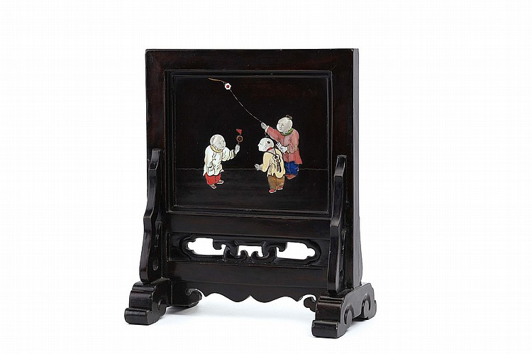 A HARDSTONE-INLAID LACQUERED WOOD 'BOYS' TABLE SCREEN. Qing Dynasty, 18th Century. Of rectangular form, the carved wood panel inlaid with various hardstones, one face decorated with three boys at play, the reverse with flowering leafy branches, all supported on a pierced wood stand, 27cm H. ? ????????????