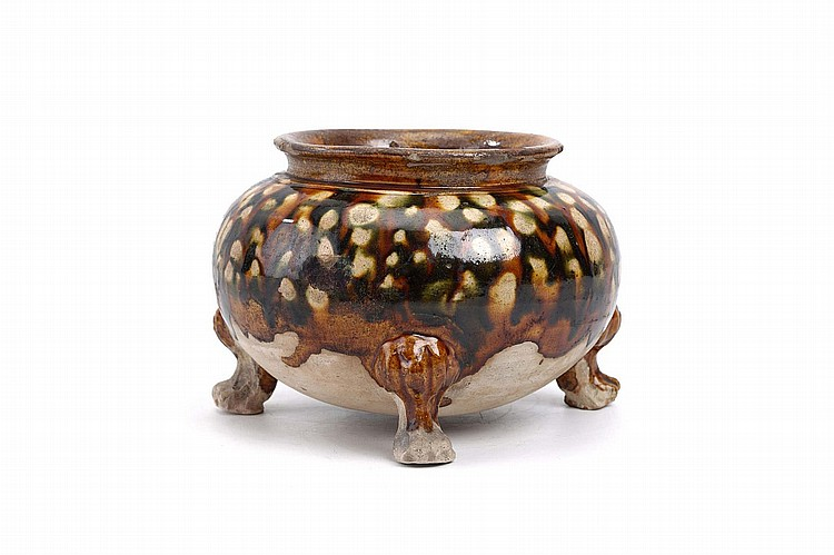 A CHINESE SANCAI-GLAZED POTTERY TRIPOD CENSER.   Tang Dynasty.   The compressed globular body supported by lion's paw feet, rising to a slightly waisted neck below an everted lipped rim, the body pattered with a green and amber glaze, 18cm H.   ? ???????