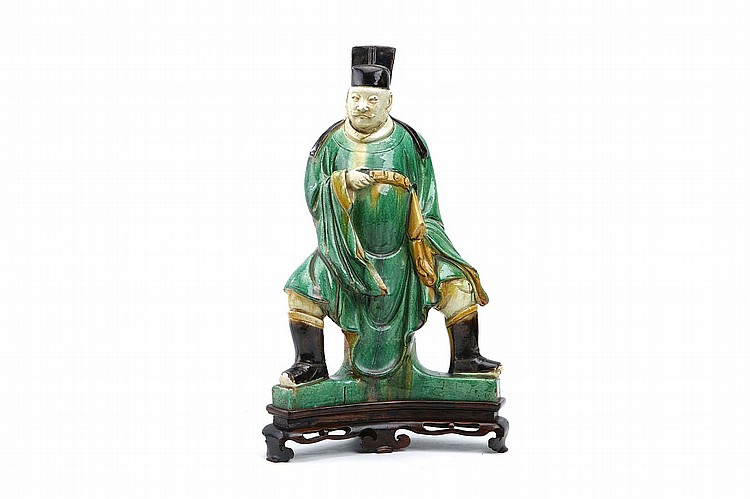 A LARGE CHINESE GLAZED FIGURE.   Ming Dynasty.    Seated with legs spread wide in flowing robes, covered in a green, yellow and brown glaze, wood stand, 44cm H.   ?  ??????