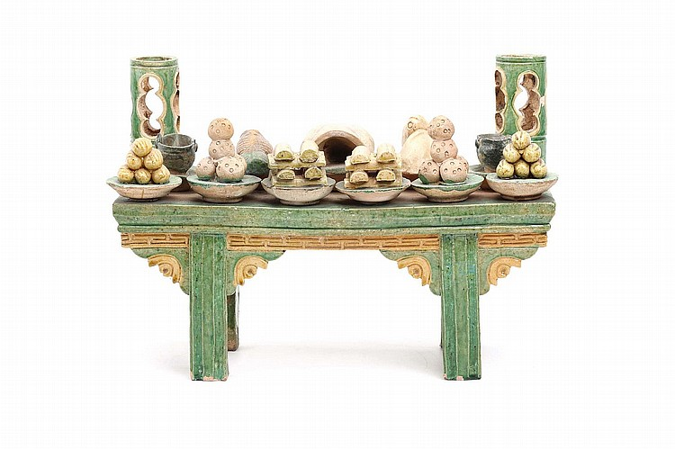 A CHINESE SANCAI-GLAZED POTTERY MODEL OF AN ALTAR TABLE BEARING THIRTEEN OFFERINGS.   Ming Dynasty.   The altar table modelled in relief, the top supporting thirteen various offerings of fish, corn, pork, ewers and other items, 24cm H.   ? ??????