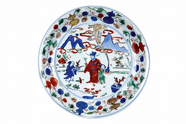 A CHINESE WUCAI DISH WITH A FIGURATIVE SCENE. Ming Dynasty, Wanli mark and of the period. Decorated in underglaze-blue and red, green and yellow enamels with a central roundel enclosing figures, surrounded by a border of double gourds, borne on leafy stems, six character mark in underglaze blue to base, 19.5cm diameter. ??? ?????? ?????????