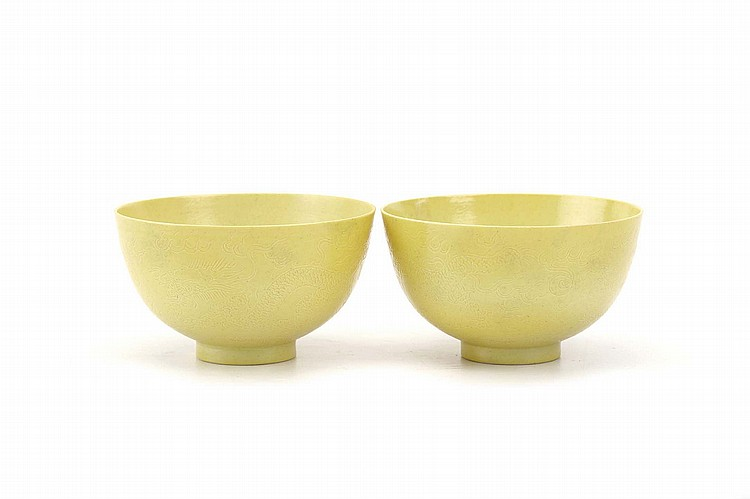 A PAIR OF CHINESE INCISED MONOCHROME YELLOW 'DRAGON' BOWLS.   Qing Dynasty, Guangxu mark and probably of the period.   The exterior incised with dragons chasing flaming pearls among flames and above a band of frothy waves, 6cm H, 10cm diameter.   ?????????