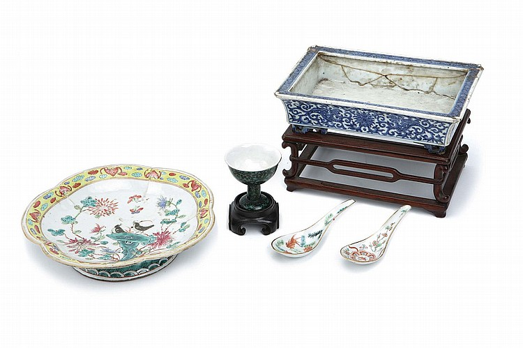 A CHINESE BLUE AND WHITE JARDINÈRE, TWO SPOONS, A FAMILLE NOIRE STEM CUP AND A FAMILLE ROSE TAZZA. Qing Dynasty. The jardinère of low rectangular form, wood stand 23 x 16 x 6cm, the spoons with Tongzhi mark to base, 13cm long, the stemcup with Qianlong nianzhi mark, 7cm H, the tazza 22cm diameter. (5) ? ?????????????????????