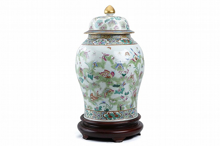 A CHINESE FAMILLE ROSE 'BUTTERFLIES' BALUSTER VASE AND COVER.   Qing Dynasty.   Decorated with a continuous pattern of butterflies above a flower-filled pond, the base and neck with a floral border punctuated with quadrefoil panels of fish alternating with flowers or gourd plants, a key-scroll border to the rim, the cover similarly decorated, and with a  gilt bud-form finial, wood stand, 63cm H.   ? ???????