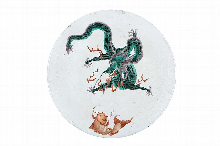 A CHINESE CIRCULAR PORCELAIN 'DRAGON AND FISH' PLAQUE.   Late Qing Dynasty.   The coiled green dragon beside a pearl with accompanying flames, looking down on the iron-red fish, itself contorted to look upward to meet the dragon's gaze, reserved on a white ground with an incised wave pattern, 27cm diameter.   Provenance: English private collection.   ?? ???