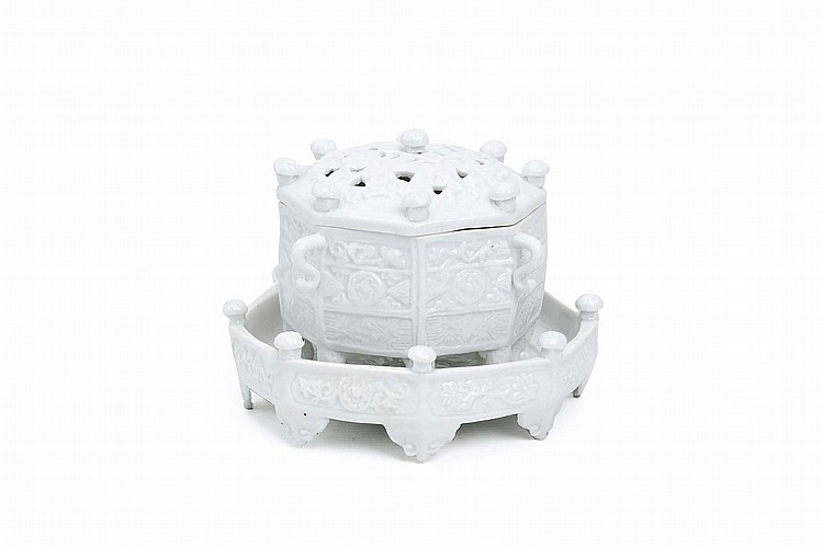 A CHINESE BLANC-DE-CHINE 'MARCO POLO' OCTAGONAL CENSER, COVER AND STAND.   Qing Dynasty, Kangxi era.    The censer moulded in relief with panels of stylised lotus flowers and foliage and set with four loop handles, the pierced domed cover carved with prunus and surmounted by nine protruding lotus buds, all raised on eight short cabriole legs, the octagonal stand similarly carved with panels of lotus around the exterior and surmounted by eight lotus buds around the gallery, the interior carved with a lotus spray encircled by leafy floral sprays, all raised on eight short ruyi feet, 10cm H. 10cm diameter, the stand 14cm diameter.   ? ?? ????????????????