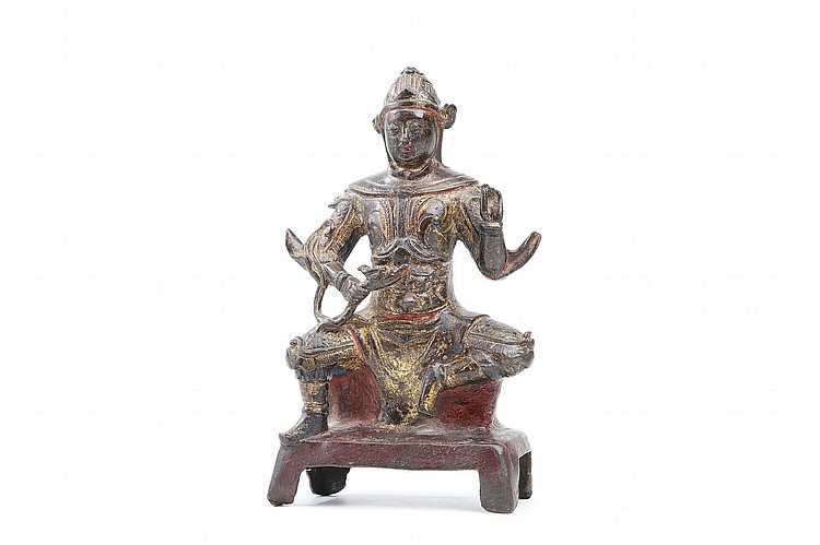 A CHINESE BRONZE FIGURE OF GUANGMU.   Yuan – Ming Dynasty.   The armoured deity, one of the four heavenly kings also known as Virupaksha, seated grasping a dragon by the neck in his right hand, the left hand raised and holding a pearl, 20cm H.   ????? ??????