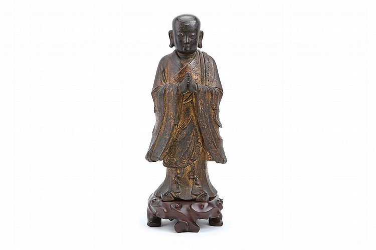 A CHINESE BRONZE STANDING FIGURE OF ANANDA. Ming Dynasty. Standing upright with hands joined in anjalimudra, dressed in wide long-sleeved monk's robes, the full face with downcast eyes and reverent expression, carved wood stand, 33cm H. Provenance: English private collection. ? ?????