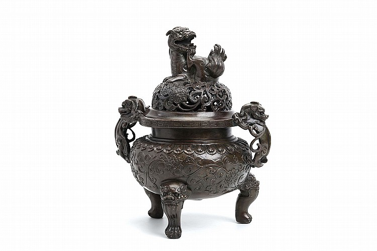A CHINESE TRIPOD CENSER AND COVER WITH BUDDHIST LION DOG FINIAL.   Qing Dynasty, Qianlong era.  The globular body supported on three lion paw feet, issuing from lion masks, rising to a straight neck with an everting rim, the elaborately pierced cover with an overall lotus scroll, surmounted by a Buddhist lion, seated the back leg scratching the lower jaw of a grinning mouth open to reveal a fierce mouthful of teeth, the body decorated with finely detailed lotus scroll with the back feet of twin lion-form handles resting on the body, their front legs resting on the rim, the heads turned back down towards the ground, Da Ming Xuande nianzhi mark to base, 28cm H.   ?? ????????????