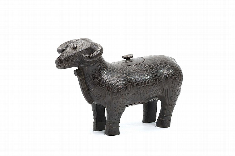 A CHINESE BRONZE MODEL OF A RAM, YANGZUN.   Qing Dynasty, 18th Century.   Standing foursquare, the head raised with curved horns and raised spherical eyes, the body incised overall with stylised fur along the body and archaistic patterns over the face and legs, the oval cover sunk flush with the top of the back, 22cm H.   ? 18?? ???