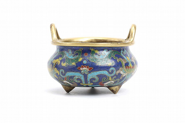 A CHINESE CLOISONNÉ ENAMEL TRIPOD CENSER.   Qing Dynasty, 18th Century.   Raised on three short conical gilt bronze feet, the squat body rising to a gilt bronze rim with loop handles above the waisted neck, the body finely worked in cloisonné enamel with an intricate pattern of scrolling flowers and foliage on a lapis blue ground, 6cm H, 9.5cm diameter.   ? ????????