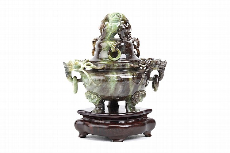 A CHINESE JADEITE CENSER AND COVER. Second half of 20th Century. The globular body supported by three lion foot legs emerging from lion-head masks, with twin openwork dragon head mask handles suspending freely moving rings, the domed cover surmounted by a carved and pierced dragon above four further handles suspending freely moving rings, wood stand, 15cm H. Provenance: Collection of Mr (1926 –) and Mrs Chen (1930 –). 20????? ??????