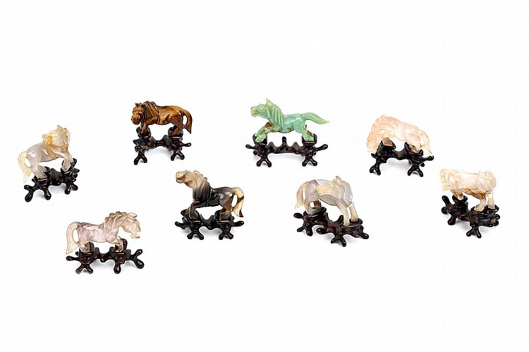 A SET OF EIGHT CHINESE HARDSTONE MINIATURE HORSE CARVINGS. 20th Century. Carved from tiger-eye, rose quartz, agate and jade, wood stands, boxed, each horse 3.5cm H. Provenance: Collection of Mr (1926 –) and Mrs Chen (1930 –). 20?? ?????????