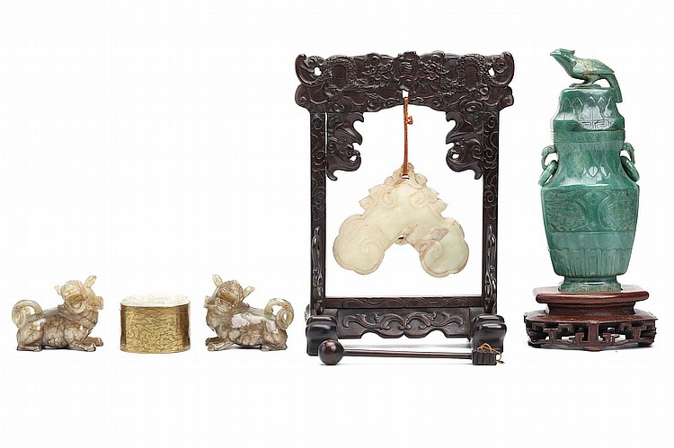A COLLECTION OF CHINESE JADE PENDANTS AND CARVINGS.   Qing Dynasty.   Comprising a jade bell, with carved wood stand and gong, a hanging jade ornament, a vase and cover with wooden stand, a pair of Buddhist lion dogs and an oval pendant with incised elephant mounted as a gilt metal box. (6)   Provenance: Collection of Mr (1926 –) and Mrs Chen (1930 –).   ? ????6?