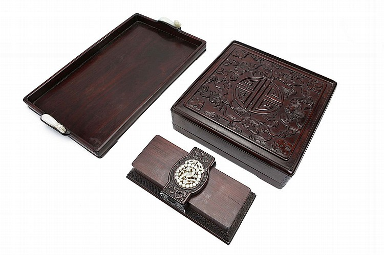 A CHINESE CARVED WOOD TRAY AND TWO BOXES. Qing Dynasty, and later. Comprising a rectangular tray, the handles formed as inset jade dragon head belt hooks, 45 x 28cm, the belt hooks 9cm long, a rectangular box and cover, the top incised with five dragons circling a stylised shou character, the box enclosing a famille rose nine-piece sweet meat set, the box 9 x 28 x 28cm, and a card case, with inset jade pendent, 7 x 24 x 11cm. (3) Provenance: Collection of Mr (1926 –) and Mrs Chen (1930 –). ????? ?????????????????????????????