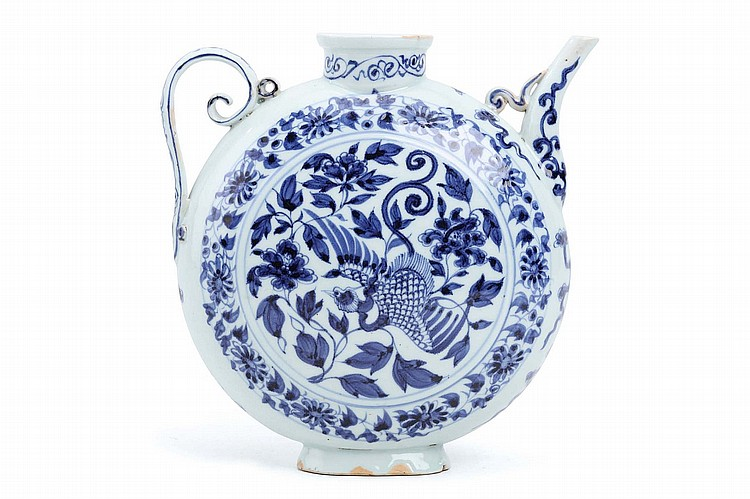A CHINESE BLUE AND WHITE EWER. The flattened circular body decorated in the Yuan dynasty style with a central roundel of a bird surrounded by lotus flowers, within a band of further scrolling flowers, another band around the cylindrical neck, a high curved spout emerging from one shoulder opposite a scrolling handle on the other side, 19cm H. ??????