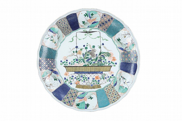 A PAIR OF CHINESE FAMILLE VERTE 'FLOWER BASKET' DISHES. Qing Dynasty, Kangxi era. The central roundel of each decorated with a lush floral bouquet encircled by twenty-four moulded cartouches each with two differently patterned designs following on from a different double cartouche scene of animals or a landscape scene, 36cm diameter. (2) ? ?? ????????? Literature: For a related single dish of identical size from the collection of the Shanghai Museum see The Complete Works of Chinese Ceramics, 2000, volume XIV, pl no 76. The Shanghai Museum dish is more simplistic in its composition with less variety in the double-cartouche scenes.
