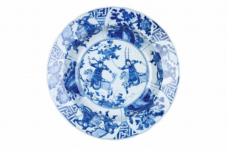 A CHINESE BLUE AND WHITE 'WARRIORS' DEEP DISH. Qing Dynasty, Kangxi mark and period. The centre with two horsebacked warriors, within a border of panels enclosing two warriors alternating with paintings of flower emerging from rocky outcrops, Da Qing Kangxi nianzhi mark to base, 24cm diameter. ? ?? ?????????