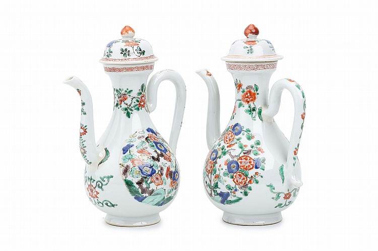 A PAIR OF CHINESE FAMILLE VERTE EWERS AND COVERS.   Qing Dynasty, Kangxi era.   The elegantly modelled pear-shaped bodies, with a C-form handle opposite and upright spout and supporting a domed cover, the body painted with two brightly coloured roundels enclosing prunus blossom, further decoration to the neck, spout and cover, 22cm H. (2)   ? ?? ???????