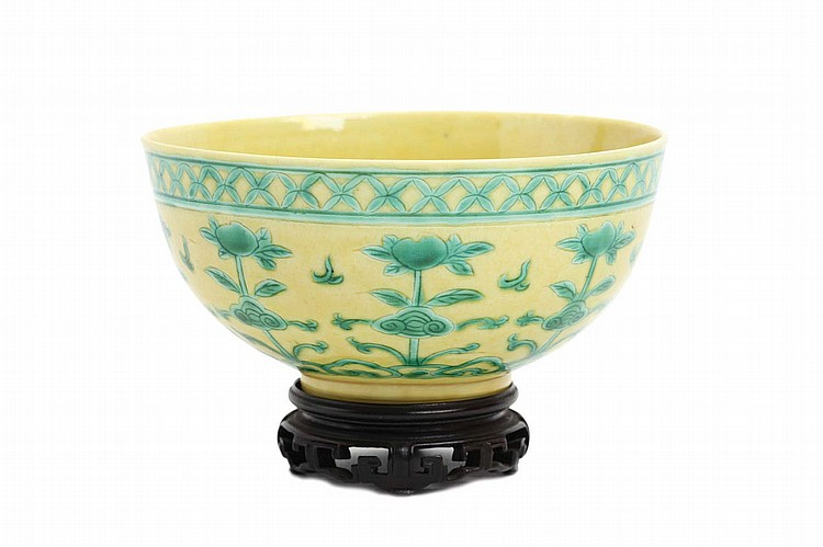 A CHINESE GREEN AND YELLOW-GLAZED BOWL.   Qing Dynasty, Kangxi mark, and probably of the period.   Incised and painted with a design of peaches above a formal cloud collar on a yellow ground, wood stand, 6cm H, 11.5cm diameter.   ? ????