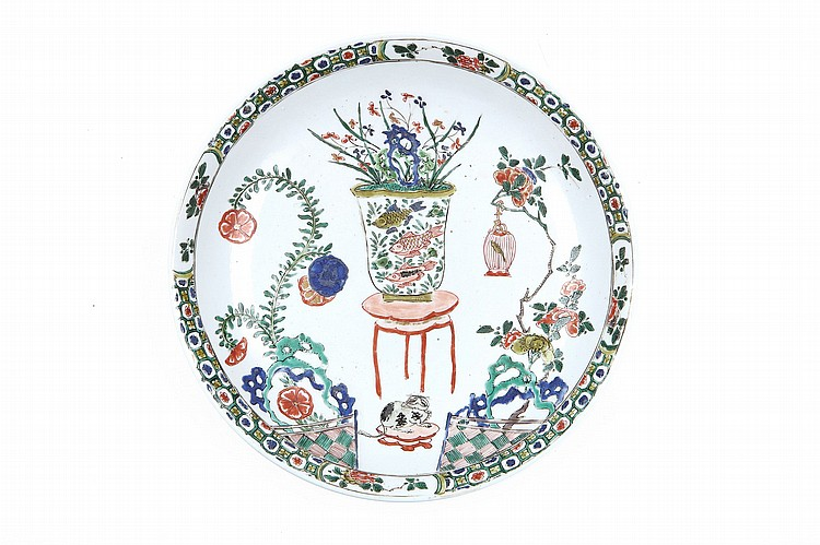 A PAIR OF CHINESE FAMILLE VERTE 'CAT AND FISH' DISHES. Qing Dynasty, Kangxi era. Painted within a thin decorative border with a fish bowl raised on a red lacquered stand between two long curling flowering branches emerging from green and blue rockwork behind a tiled floor, one branch supporting a caged bird, a cat, raised on a stand in the foreground greedily eying the fish, 27.5cm diameter. (2) ? ?? ????????