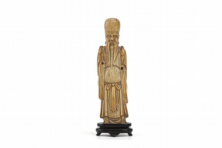 A CHINESE CARVED IVORY STANDING FIGURE.   Ming Dynasty.   Standing in a long flowing robe, the eyes downcast, with a long beard and a bald head, 16cm H.   ? ??? ????