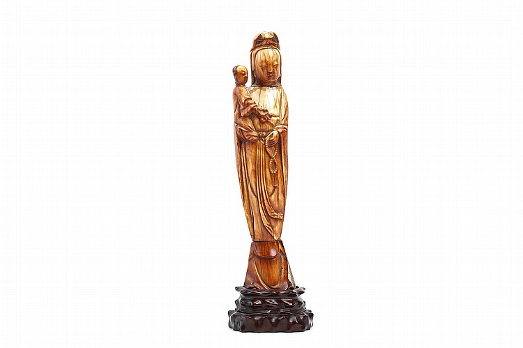 A CHINESE IVORY 'GUANYIN AND CHILD' CARVING.   Ming Dynasty.   Standing with the child held up to the right shoulder, a rosary held in the left hand, wood stand, 22cm H.   ? ???????   Literature: For a similar figure see Chinese Ivories from the Shang to the Qing, the Oriental Ceramic Society, 1984, cat no 20.