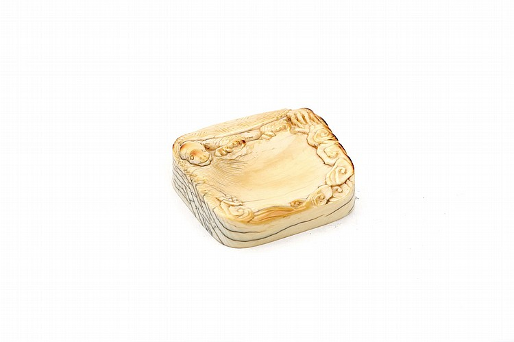 A CARVED IVORY WASHER.   Qianlong mark and probably of the period.   Of square form with rounded corners, the top with a turtle clambering over the sides, with scrolling clouds carved around the edge of the well, carved Qianlong nianzhi mark to base, 4 x 4cm.   ???? ???????
