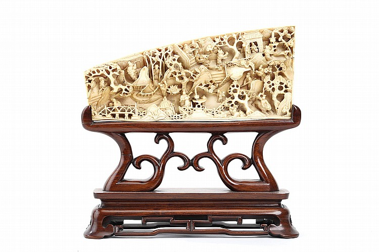 "AN CHINESE IVORY CARVED 'TWENTY-FOUR PARAGONS OF FILIAL PIETY' PLAQUE.   Early 20th Century.   Deeply carved to one side with a landscape panorama enclosing various scenes including Jiang Ge carrying his mother and Tan Zi discussing with hunters whilst disguised as a deer, carved wood stand, 23cm long.   20???? ""????""????"