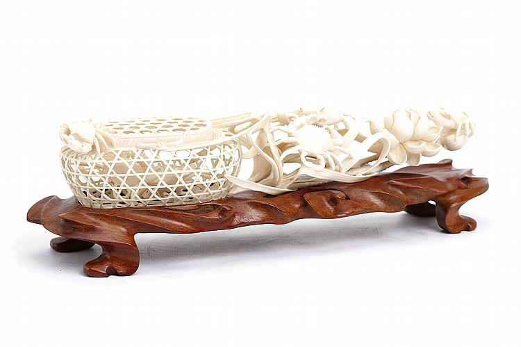A CHINESE IVORY CARVING OF CRABS IN A NET.   Late 19th / early 20th Century.   Impressively carved as a woven net enclosing a crab, besides foliage and a blooming lotus flower, over which several further crabs are clambering, 29cm long.   19?????20????  ?????????