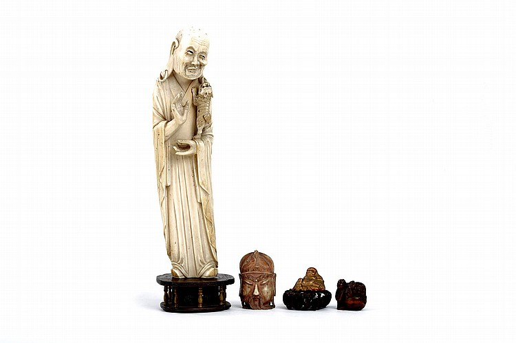 A CHINESE CARVED IVORY FIGURE OF A LUOHAN. Late Qing Dynasty. Standing in flowing robes, holding a small lion in the left hand which is biting the earring hanging from the left ear, whilst the right hand is raised, and the mouth contorted into an expression of amusement and titillation, on a wood stand, 26cm H, together with an ivory head, a carved Buddha and stand, and a wood netsuke. (4) ?? ??????