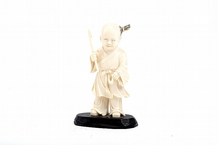A CHINESE IVORY CARVING OF A BOY. Qing Dynasty. Standing holding a stick in the right hand, 12cm H. ? ?????