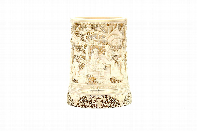 A CHINESE CARVED IVORY BRUSH POT. Qing Dynasty. Of cylindrical form, carved and pierced with a continuous scene of figures in landscape beneath pines, raised on an integral carved and pierced floral base, 12cm H. ? ????
