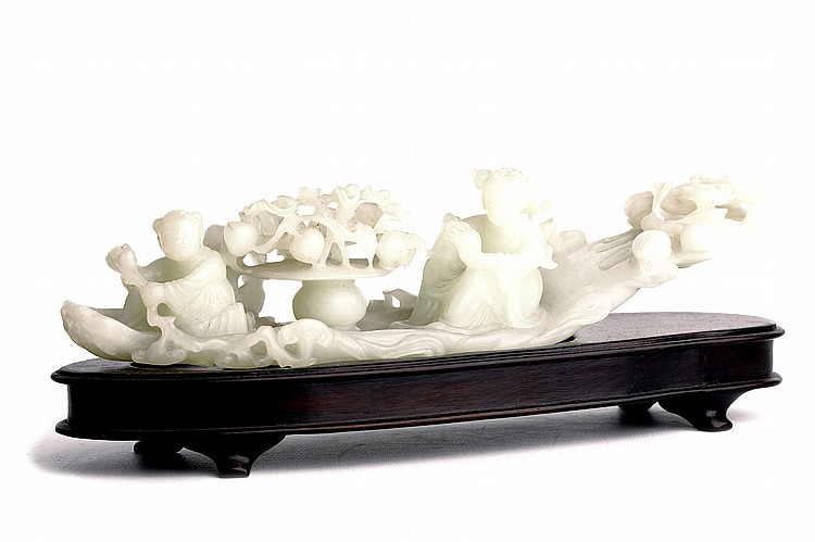 A CHINESE JADE CARVED 'RAFT GROUP'. Second half of 20th Century. Carved and pierced to depict a boy at the front paddling with a long sprig of lingzhi fungus, separated from a seated lady by a basket of fruit, wooden stand, 23cm long. Provenance: Purchased in Taiwan in the 1990s. 20????? ??????