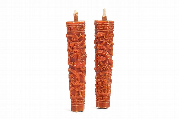 A PAIR OF CHINESE MOULDED WAX 'DRAGON' CANDLE STICKS.   Of tapering form and hexagonal section, each moulded with a five-clawed dragon among scrolling clouds, 17.5cm H. (2)   ??????
