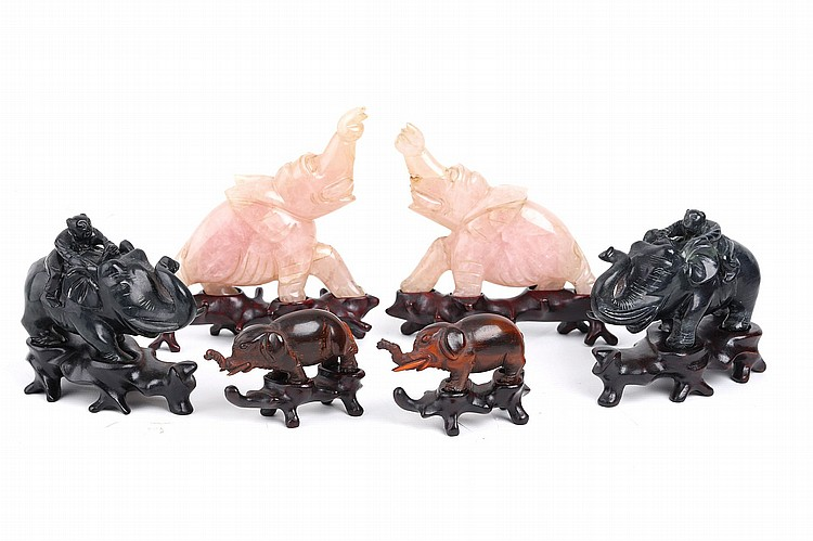THREE PAIRS OF CHINESE CARVED ELEPHANTS.   Qing Dynasty / Republican era.   One pair carved in black hardstone, 7cm H, another pair of rose quartz, 11.5cm H, and another of carved horn, 5cm H, each with carved wood stands. (6)   Provenance: Brian Pearson (1926 – 2003) Collection, acquired in China between 1945 and 1946.   ??/???? ??????????????????