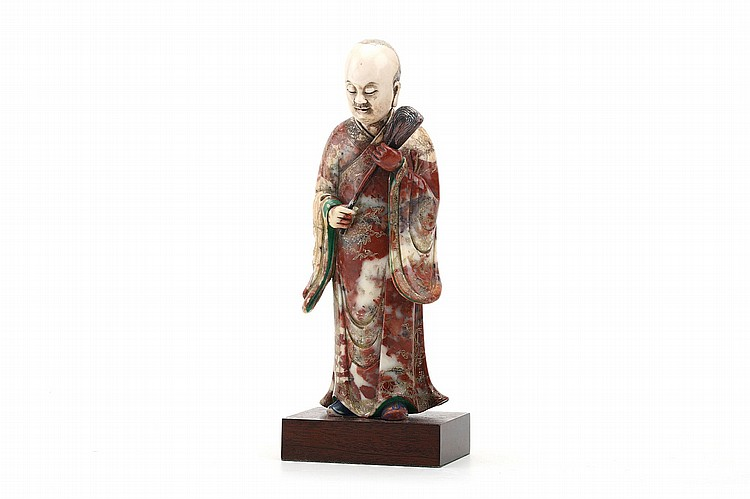 A CHINESE SOAPSTONE MODEL OF A LUOHAN.   17th / 18th Century.    Standing in long flowing robes with incised patterns holding a fly whip between his two hands, head and eyes slightly lowered, 23cm H.   17-18?? ????????