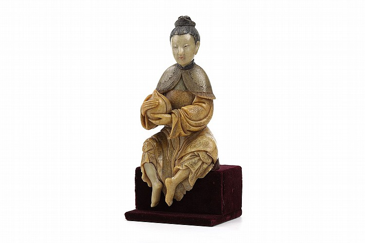 A CHINESE SOAPSTONE MODEL OF A LADY. 17th / 18th Century. Seated, holding a large peach, in trailing robes, the feet bare, red velvet stand, 19.5cm H. Provenance: Spink & Sons, by repute. 17-18?? ??????????