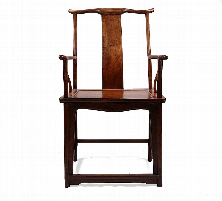 A CHINESE HUANGHUALI YOKEBACK ARMCHAIR. Qing Dynasty. With a wide scrolling crest rail and rounded terminals, shaped above a curved vertical splat, the curved arm rails terminating in rounded out scrolled handgrips, with shaped supports to the rectangular seat, all resting on plain legs below a shaped apron, the feet united by stretchers, 110cm H. ???? ??????