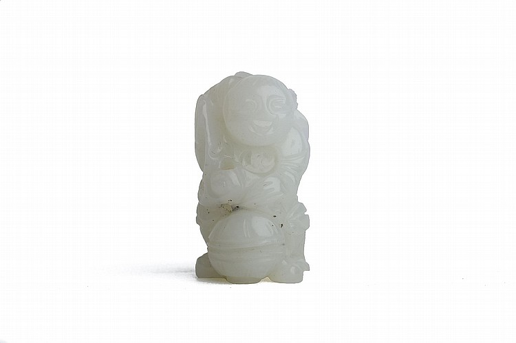 A CHINESE WHITE JADE CARVING OF A BOY.   Qing Dynasty, 18th / 19th Century.   The miniature figure grinning widely and standing huddled over a ball, 3.3cm H.   ? ????