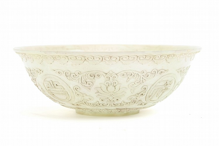 A CHINESE CARVED JADE BOWL.   20th Century.   Decorated with lotus flowers and scrolling foliage, with four circular panels each enclosing a Chinese character, a band of ruyi heads at the rim, and a lappet border at the base, 7.5cm H, 22cm diameter.   20?? ????????