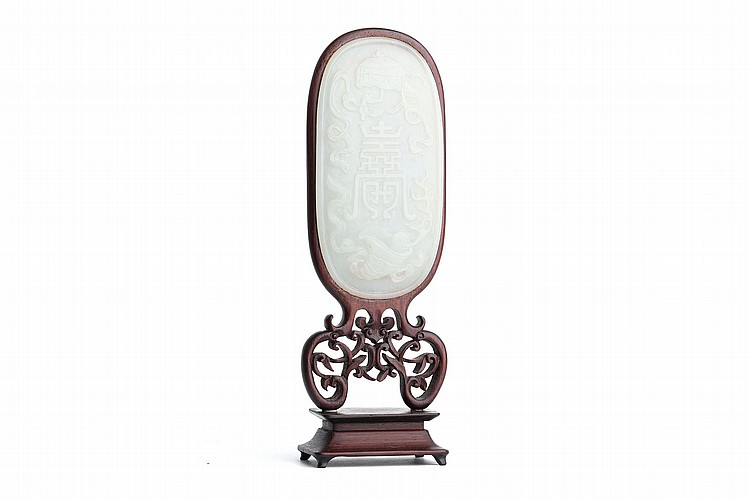 A CHINESE CARVED JADE OVAL PLAQUE.   Qing Dynasty, 18th Century.   The jade plaque incised with a stylised shou character, mounted in a carved and pierced wood stand, the jade 13.5cm long.   ?18?? ????????
